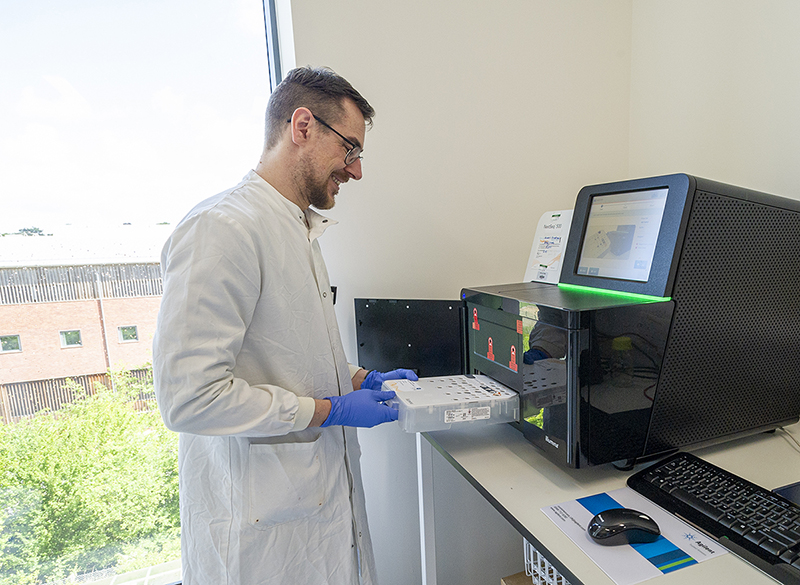 scientist loading a sequencing machine